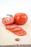 Tomatoes. Cut by a kitchen knife on a wooden board Stock Images