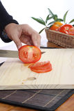 Tomatoes. Cut by a kitchen knife on a wooden board Royalty Free Stock Image