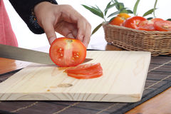 Tomatoes. Cut by a kitchen knife on a wooden board Royalty Free Stock Images