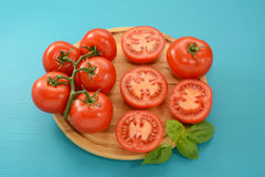 Tomatoes - cut, whole and on the vine with fresh basil Royalty Free Stock Photo