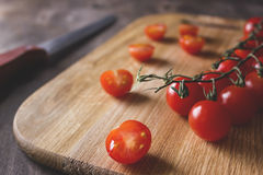 Tomatoes on a cutting board. Group cherry red tomatoes on a cutting board with a knife on a wooden background Stock Photography