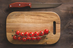 Tomatoes on a cutting board. Group cherry red tomatoes on a cutting board with a knife on a wooden background Stock Images