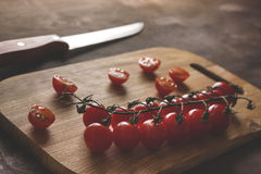 Tomatoes on a cutting board. Group cherry red tomatoes on a cutting board with a knife on a wooden background Royalty Free Stock Photos