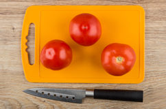 Tomatoes on cutting board and kitchen knife on table Stock Photo