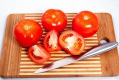 Tomatoes on a cutting board. Red ripe tomatoes and a knife on a cutting board Royalty Free Stock Images