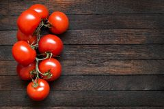 Tomatoes on dark oak table with copy space. Fresh red tomatoes on branch on dark brown oak table. Copy space. Burnt wooden texture. Top view. Horizontal stock photography