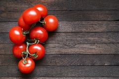 Tomatoes on dark wooden table with copy space. Fresh red tomatoes on branch on dark brown wooden table. Oak texture. Top view. Copy space. Horizontal orientation royalty free stock images