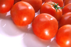 Tomatoes diagonal. Display of a group of market fresh tomatoes with odd one out Royalty Free Stock Photo