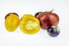 Tomatoes, different colors,  closeup on a white background. Royalty Free Stock Photos