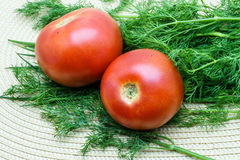 Tomatoes and dill on a napkin. Tomatoes and dill on a wicker napkin royalty free stock photos
