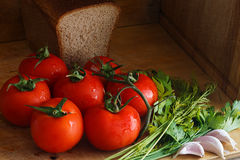 Tomatoes, dill, parsley, garlic on a wooden table Stock Photography