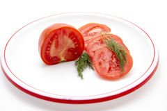 Tomatoes with dill on plate Stock Photos