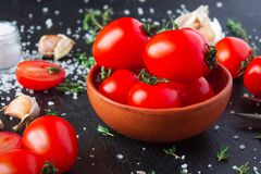 Tomatoes in a dish on a black background. Tomatoes in preparation. Tomatoes for the sentencing of lettuce and other dishes. The cook prepares dishes from stock photography
