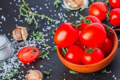 Tomatoes in a dish on a black background. Tomatoes in preparation. Tomatoes for the sentencing of lettuce and other dishes. Cook prepares dishes from tomatoes royalty free stock photo