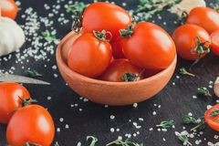 Tomatoes in a dish on a black background stock image