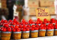 Farmer's market tomatoes displayed in wooden baskets with a funny sign Royalty Free Stock Image