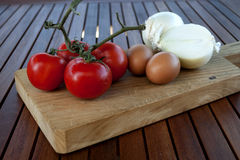Tomatoes, eggs and onions. On a chopping board Royalty Free Stock Image