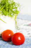 Tomatoes and fennel on blue tablecloth Stock Photos