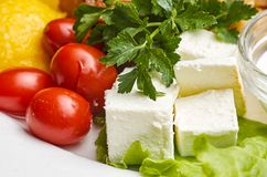 Tomatoes feta cheese. Feta cheese cut in cubes, vegetables, herbs and olive oil-the ingredients for a greek salad Royalty Free Stock Photography