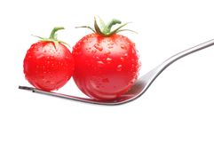 Tomatoes On Fork. Fresh tomatoes on fork, a bigger and smaller one. Isolated on white background. Balance concept Stock Photos