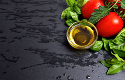 Tomatoes and fresh basil leaves with olive oil Stock Photo