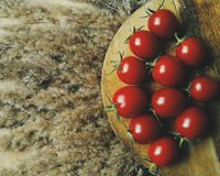Tomatoes. Fresh tomatoes, red, food, dry grass, spikelet royalty free stock images