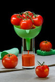 Tomatoes in a funnel in  glass with tomato juice. Tomatoes in a funnel in a glass with tomato juice on a table Stock Photos
