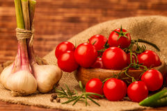 Tomatoes and garlic. Fresh, ripe cherry tomatoes and garlic on an old burlap Stock Photography