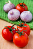 Tomatoes and garlic. On wooden table and green towel Stock Photo