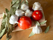Tomatoes garlic and a bay leaf Royalty Free Stock Images