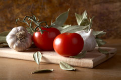 Tomatoes garlic and bay leaf branches on  table Stock Photography