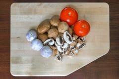 Tomatoes Garlic and Portobello Mushroom on Cutting Board. Tomatoes Garlic Cloves Baby Portobello Mushrooms on Kitchen Cutting Board closeup Royalty Free Stock Images