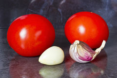 Tomatoes and garlic. On a dark background Stock Photography