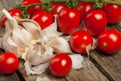 Tomatoes and garlic. Fresh tomatoes and gloves of garlic on the wood royalty free stock images