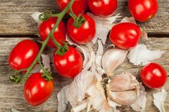 Tomatoes and garlic. Fresh tomatoes and gloves of garlic on the wood Stock Photos