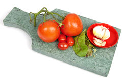 Tomatoes and garlic on a green marble cutting board Stock Images