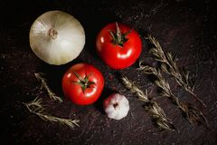 Tomatoes, garlic, onion and rosemary on a black background close-up table top Stock Photos