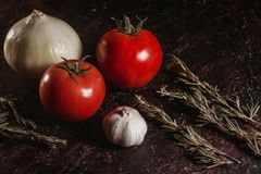 Tomatoes, garlic, onion and rosemary on a black background close-up ingredients table top Royalty Free Stock Photo