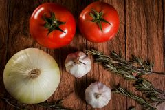 Tomatoes, garlic, onion and rosemary on a wood background close-up ingredients table top Stock Photos
