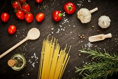 Tomatoes garlic salt olive peppers and pasta on a black table stock images