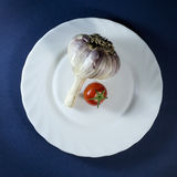 Tomatoes and garlic in white plate on blue background. Tomatoes and clove of garlic in white plate on a dark blue background stock image