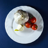 Tomatoes and garlic in white plate on blue background. Tomatoes and clove of garlic in white plate on a dark blue background stock photography