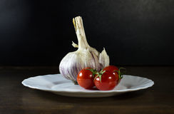 Tomatoes and garlic in white plate. Tomatoes and clove of garlic in white plate royalty free stock photos