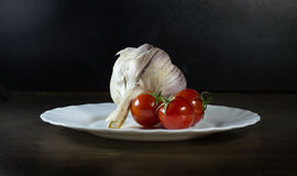 Tomatoes and garlic in white plate. Tomatoes and clove of garlic in white plate royalty free stock photo