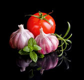 Tomatoes and garlic in wooden plate on black backg Royalty Free Stock Photos