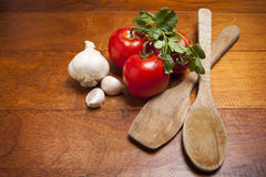 Tomatoes and garlic with wooden spoons Royalty Free Stock Image
