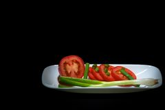 Tomatoes and Geen Oinions. Sliced tomatoes and green onions on a white plate spot lit on black Royalty Free Stock Photos
