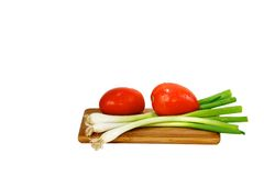 Tomatoes and Geen Oinions. Tomatoes and green onions on a cutting baord on white background Stock Image