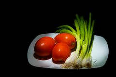 Tomatoes and Geen Oinions. Whole tomatoes and green onions on a white plate spot lit on black Royalty Free Stock Photo