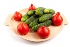 Tomatoes and gherkins. On a wooden board isolated on white background Stock Photography